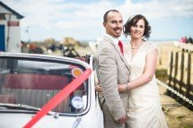 bride and groom with vintage morris minor wedding car on devon beach